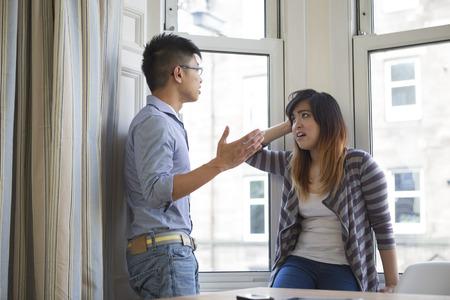 Jeune couple chinois soutenant dans leur salon.