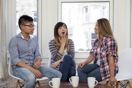 yawning: Group of three Asian friends at home talking to each other. Woman in the middle is yawning. Concept about being bored and tired. Stock Photo
