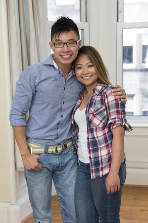 Yound and happy Chinese couple posing together at home photo