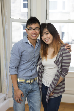 young couple smiling: Yound and happy Chinese couple posing together at home