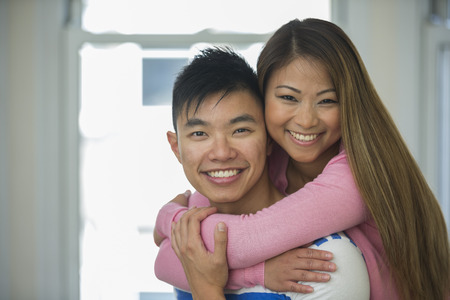 Portrait of happy Asian Couple together in there living room at home. Looking at camera photo