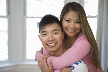 filipino adult: Portrait of happy Asian Couple together in there living room at home. Looking at camera