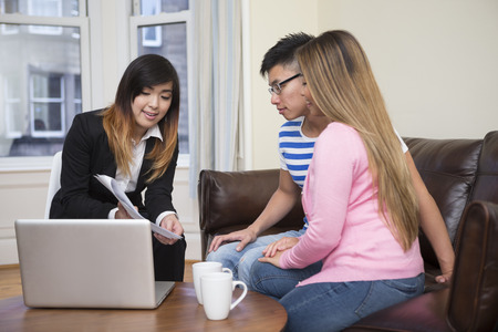 explaining: Asian couple meeting financial adviser for investment planning.