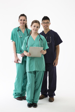 chinese medical: A group Portrait of three multi-ethnic healthcare workers wearing uniforms. Caucasian & Chinese Medical team Isolated on a White Background. Stock Photo