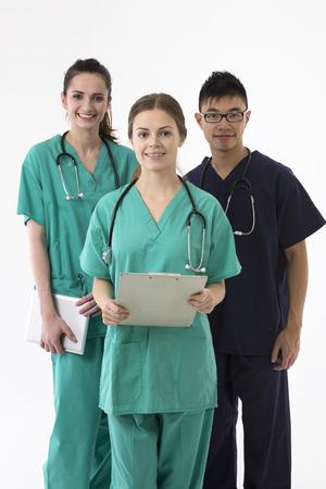 grupo de médicos: Un retrato de grupo de tres trabajadores de la salud multiétnica con uniformes. Equipo médico de raza caucásica y chino aislado en un fondo blanco.
