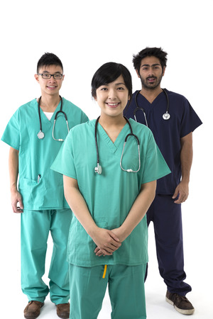 chinese adult: A group Portrait of three multi-ethnic healthcare workers wearing uniforms. Medical team Isolated on a White Background. Stock Photo