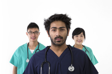 healthcare workers: A group Portrait of three multi-ethnic healthcare workers wearing uniforms. Medical team Isolated on a White Background. Stock Photo