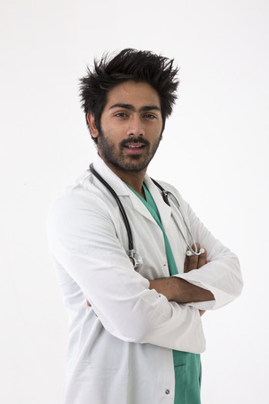 Male Indian doctor wearing a white coat and stethoscope. Isolated on white background. photo