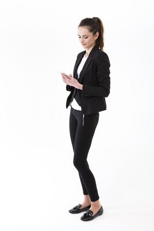 persona caminando: Empresaria con estilo joven usando el tel�fono m�vil. Aislado en el fondo blanco. Retrato de longitud completa de un modelo de mujer morena de raza cauc�sica.