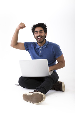 Happy Indian man using a laptop PC and cheering. Isolated on White Background.