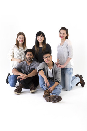 group of young adults: Happy group of friends sitting on floor. Mixed race group. Isolated on a white background.