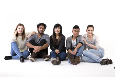 Happy group of friends sitting on floor. Mixed race group. Isolated on a white background. photo