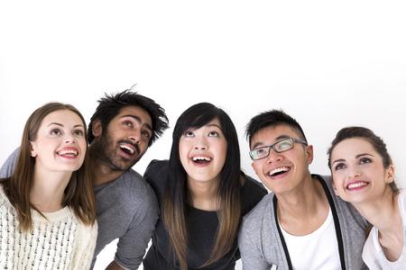 Felice gruppo di amici guardando in alto sopra di loro. Gruppo di razza mista. Isolato su uno sfondo bianco.