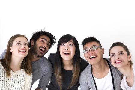 Happy group of friends looking up above them. Mixed race group. Isolated on a white background.