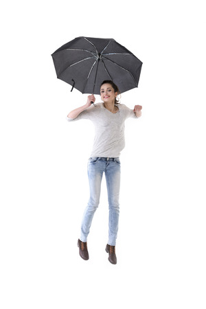 weather protection: Full-length image of a Caucasian woman wearing casual clothes and standing under an umbrella. Isolated on White Background.