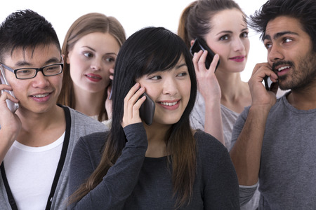 group of young adults: Happy group of friends talking on there Smartphones. Mixed race group. Isolated on a white background.