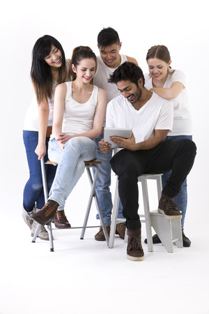 Happy group of friends using Tablet PC device. Mixed race group. Isolated on a white background. photo