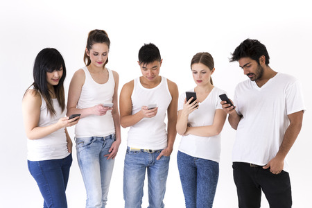 group of young adults: Happy group of friends using there Smartphones. Mixed race group. Isolated on a white background.