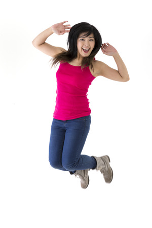 Excited & happy Asian woman jumping for joy. Chinese ethnicity, isolated on white background.