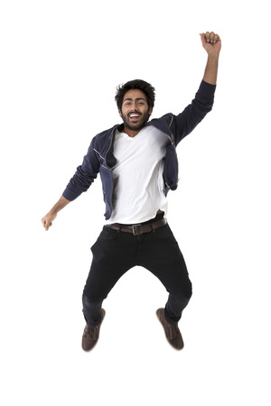 asian indian: Excited Indian man jumping for joy. Isolated on white background.