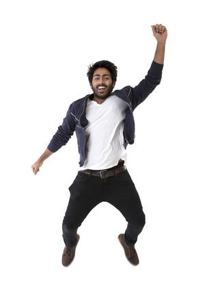 boy jumping: Hombre indio emocionado que salta de alegr�a. Aislado en el fondo blanco.