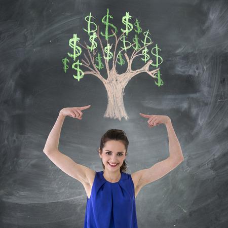 Happy Caucasian woman in front of chalk money tree drawing on blackboard. photo