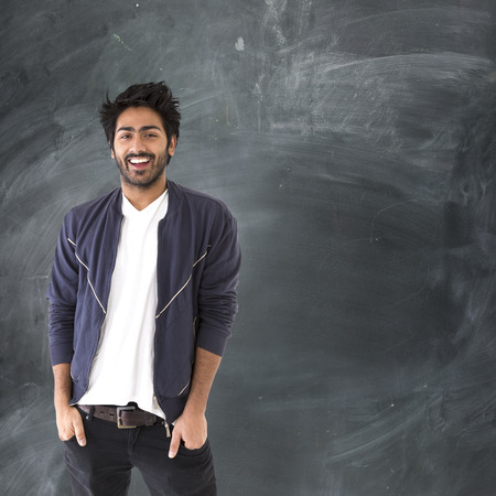 indian ethnicity: Portrait of a happy Indian man standing next to a blackboard.