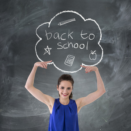 female teacher: Happy Caucasian Woman pointing at Back to School concept hand drawn on chalkboard. Stock Photo