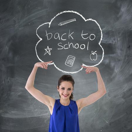 """maestra enseñando: Mujer caucásica feliz que señala en """"Volver a la escuela"""" concepto dibujado a mano en la pizarra. Foto de archivo"""