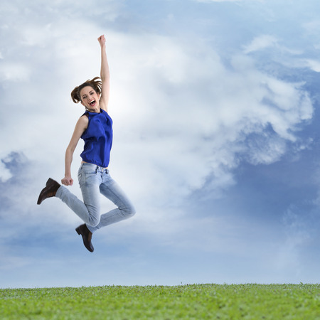 Excited & happy woman jumping for joy. Caucasian ethnicity,