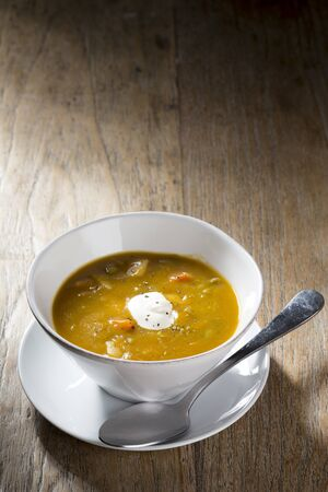 wholesome: Vegetable soup on a wooden table. Rustic and wholesome homemade vegetable stew.