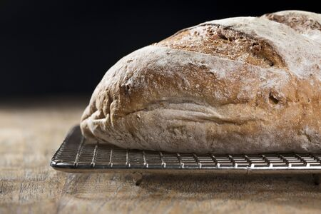 artisan bakery: Close up view of a rustic loaf of bread on an old wooden table. Stock Photo