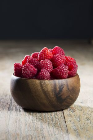Bowl of raspberries sitting on a rustic wooden table. photo