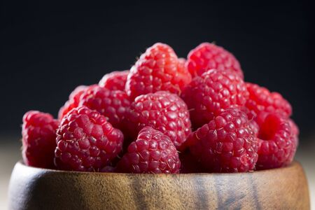 Clos up of a bowl of raspberries sitting on a rustic wooden table. photo