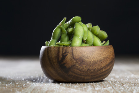 Bowl of edamame sitting on a rustic wooden table.