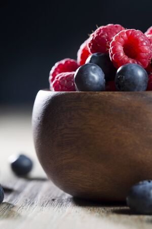 Bowl of fresh berries sitting on a rustic wooden table. photo