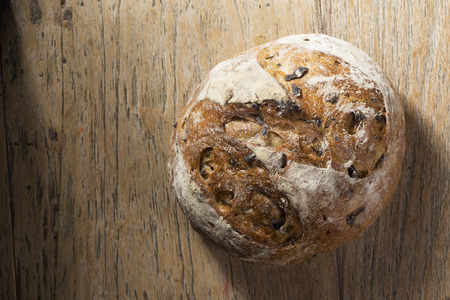 Above view of a rustic loaf of bread on an old wooden table. Archivio Fotografico