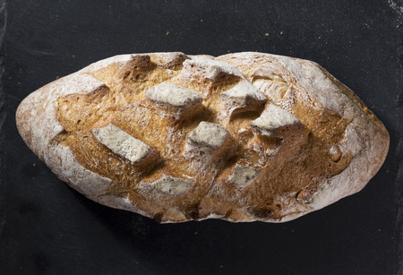Rustic bread loaf on Black Slate Board.
