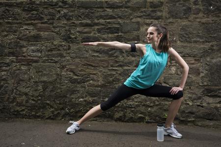 atletismo: Mujer atlética estiramiento antes o después del entrenamiento