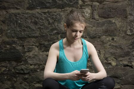 atleta: Athletic woman looking at Smart Phone after training Foto de archivo