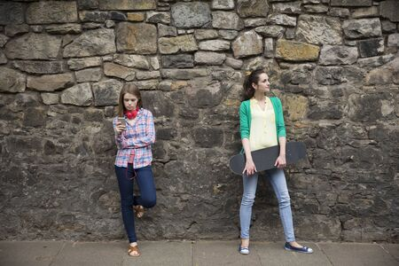 looking away from camera: Two fashionable women leaning against a wall, one with a skateboard. looking away from camera.