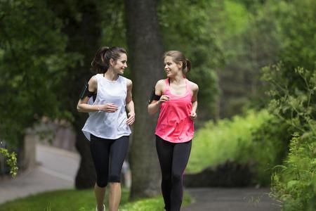 Twee atletische vrouwen lopen buiten Stockfoto