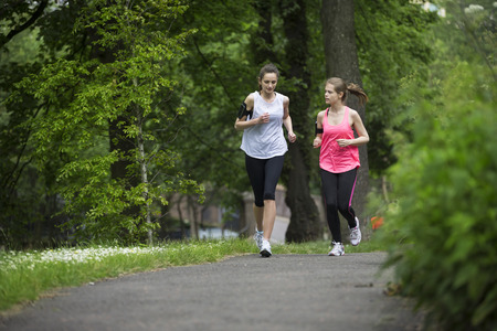 athletic women: Two athletic women running outdoors Stock Photo