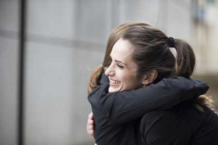 two girls hugging: Two happy Businesswomen hugging each other outside office building. Stock Photo