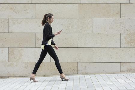 persona caminando: Vista lateral de un feliz caucásica Empresaria caminar en la calle de la ciudad mediante un teléfono inteligente.