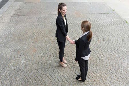 unusual angle: Elevated view of two Caucasian business women shaking hands. Stock Photo