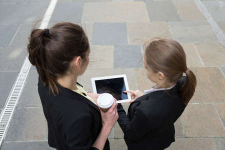 using tablet: Elevated view of two Caucasian Business women using digital tablet computer.