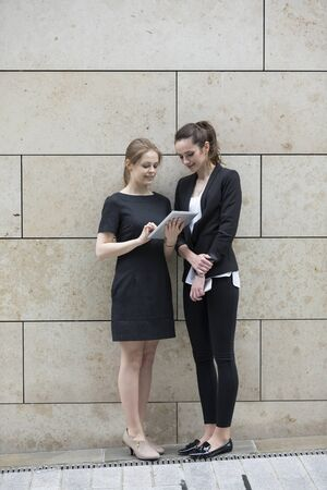 women business: Two Caucasian Business women using digital tablet computer, leaning against a marble wall.