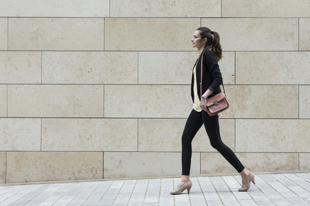 person walking: Side view of a Caucasian Businesswoman walking on city street in front of modern marble wall.