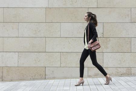 caminando: Vista lateral de un caucásico empresaria caminando en la calle de la ciudad delante de la pared de mármol moderna.